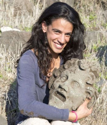 A member of the archaeological team holds the bronze mask of the god Pan, uncovered at the University of Haifa's excavation at Hippos-Sussita. (University of Haifa)