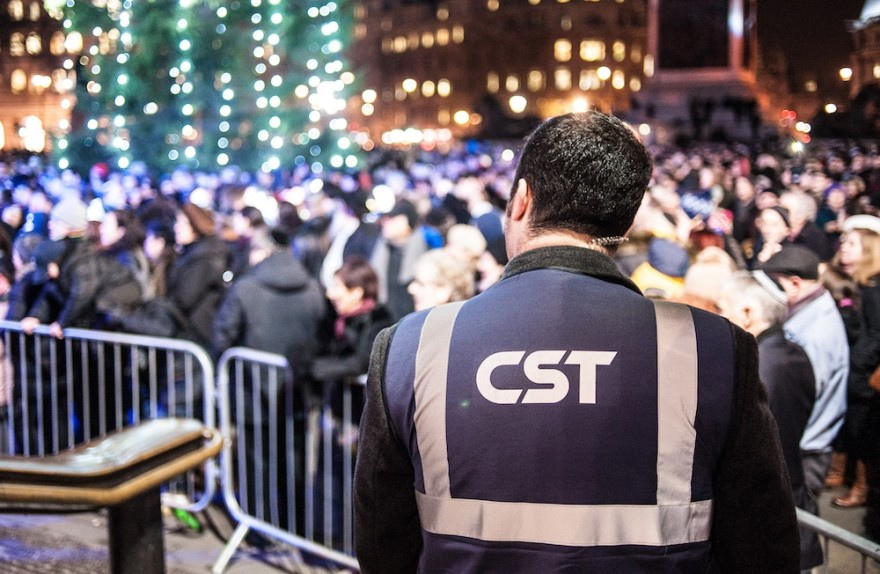 A Community Security Trust guard keeps watch over a Hanukkah celebration in London in 2014. (Blake Ezra Photography)
