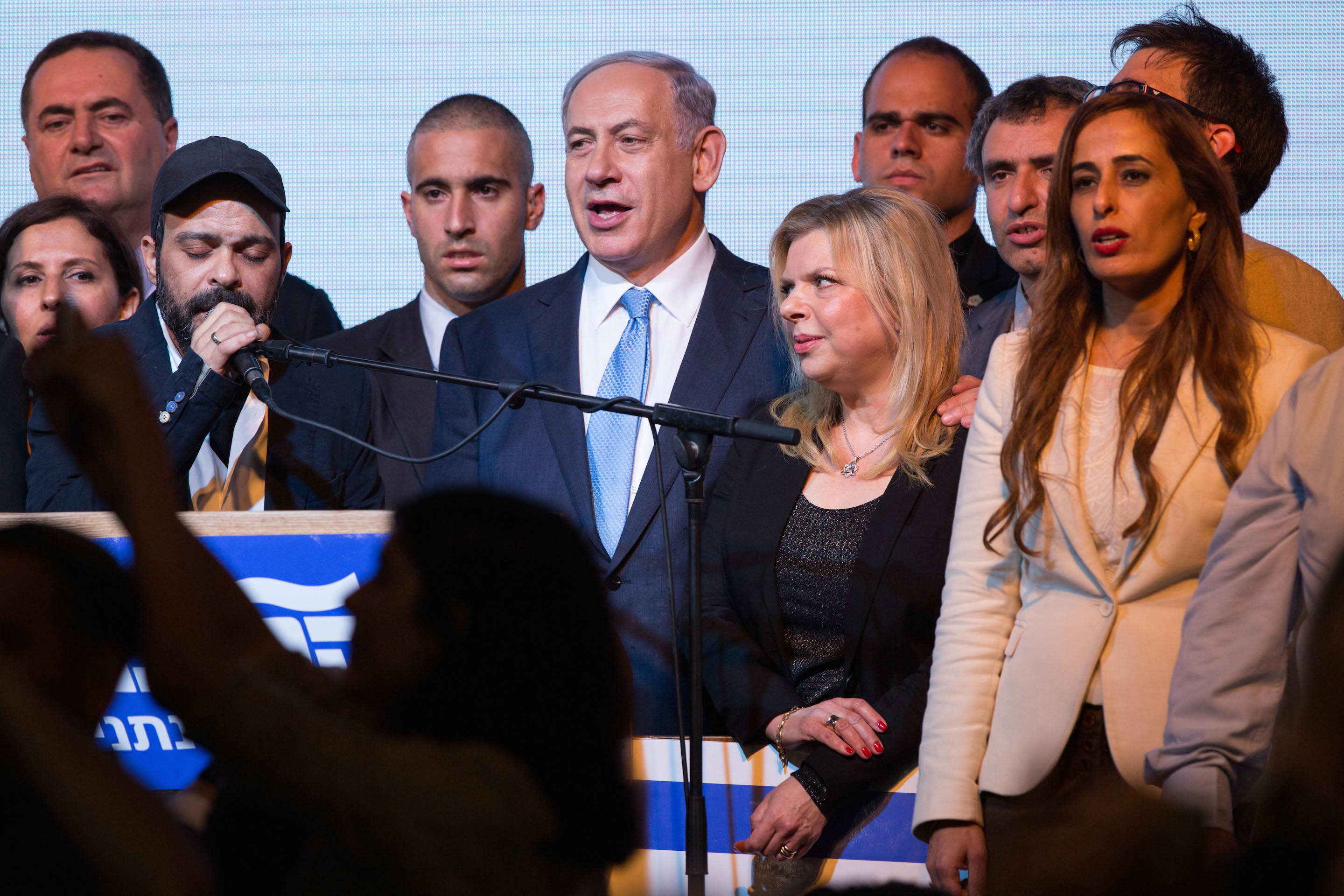 Israeli Prime Minister Benjamin Netanyahu and his wife, Sara, sing the Israeli anthem along with members of his Likud party, at the party headquarters in Tel Aviv, March 18, 2015, after the exit polls in the Israeli general elections were announced, with Netanyahu claiming victory. (Miriam Alster/FLASH90)