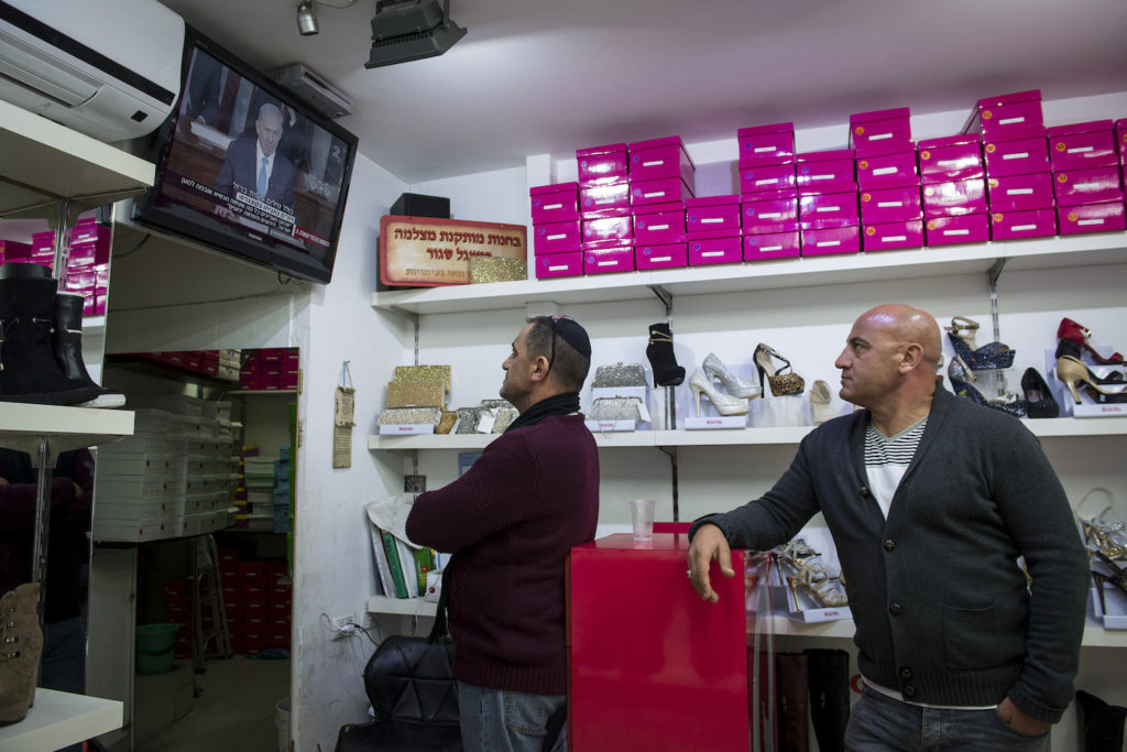 Israeli shopkeepers watch Israeli Prime Minister Benjamin Netanyahu's speech to a joint meeting of the U.S. Congress, on a television, Jerusalem, March 3, 2015. (Danielle Shitrit/Flash90)