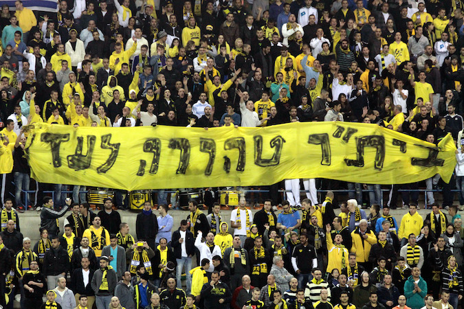 "Fans of the Beitar Jerusalem soccer team held up a banner saying ""Beitar Pure Forever"" and chanted against owner Arcadi Gayadamak in protest of Gaydamak's decision to sign two Muslim players, Jan. 26, 2013. (Flash90)"