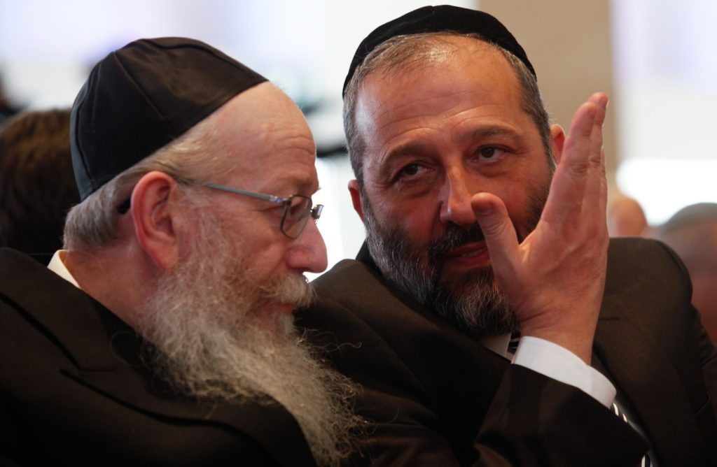 Shas party leader Aryeh Deri, right, and Yaakov Litzman, head of United Torah Judaism, at the opening session of the 20th Israeli parliament, March 31, 2015. (Nati Shohat/Flash90)