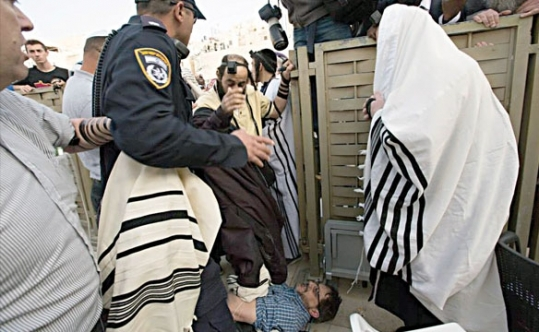 Alden Solovy, on the ground, being stomped on by another worshipper at the Western Wall.