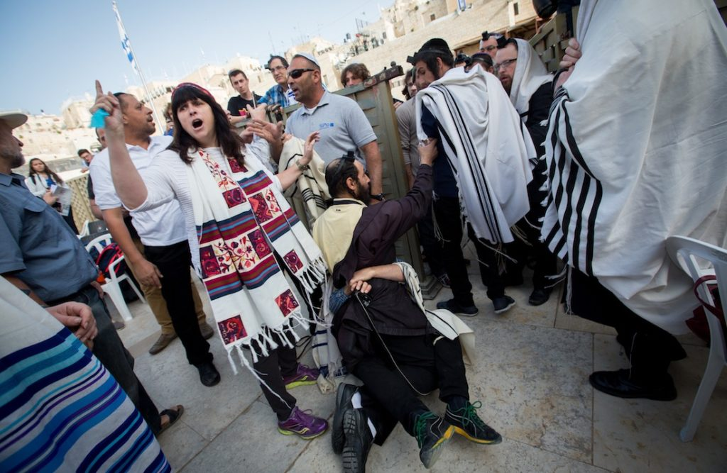 An orthodox man scuffles with a supporter of Women of the Wall, a group advocating for women's prayer at the Western Wall, April 20, 2015. (Miriam Alster/Flash90)