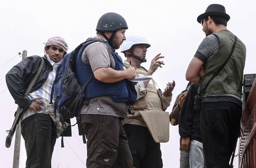 In this handout image made available by the photographer, American journalist Steven Sotloff, center with black helmet, talks to Libyan rebels on the Al Dafniya front line, about 15 miles from Misrata, Libya, June 2, 2011. Sotloff was beheaded in September 2014 nearly a year after being kidnapped in Syria. (Etienne de Malglaive via Getty Images)