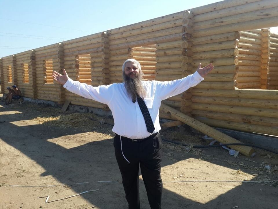 Rabbi Moshe Azman posing in front of houses under construction in Anatevka. (Courtesy: Anatevka)
