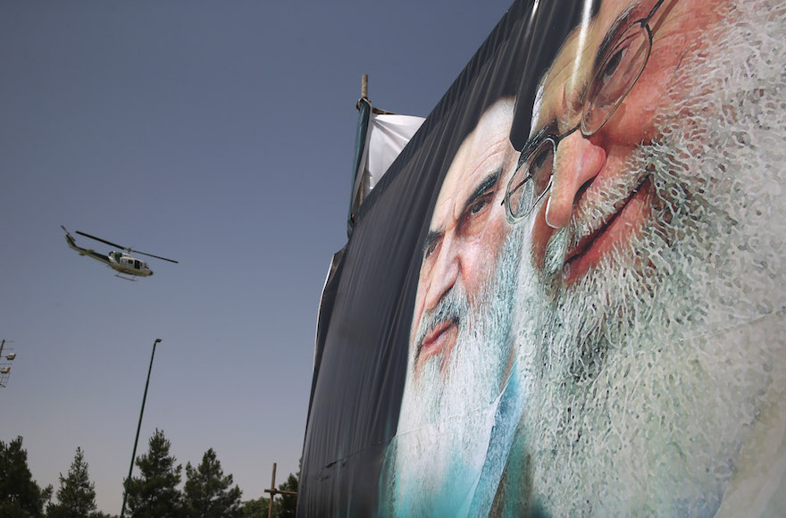 An Iranian police helicopter passes by portraits of Iran's supreme leader Ayatollah Ali Khamenei, right, and the former Ayatollah Khomeini, in Tehran, Iran, June 4, 2015. (John Moore/Getty Images)