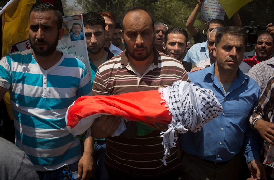 Surrounded by her relatives, the body of the 18-month-old baby Ali Saad-Dawabsheh is carried during her funeral in the Palestinian village of Duma, in the West Bank, on July 31, 2015. (Oren Ziv/Getty Images)