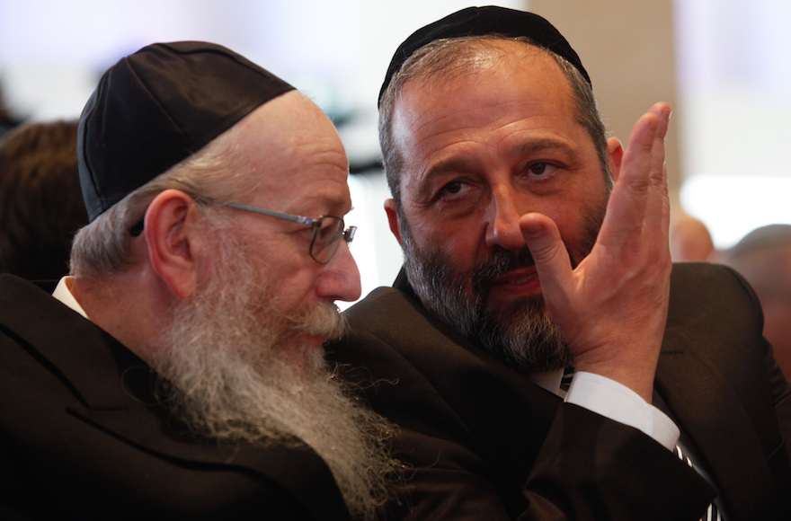 Shas party leader Aryeh Deri, right, speaks with United Torah Judaism leader Yaakov Litzman at the opening session of the 20th Knesset on March 31, 2015. (Nati Shohat/Flash90)