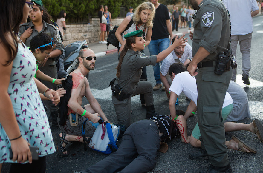 Police officers and civilians attending to a victim of a stabbing at the annual gay pride parade in Jerusalem, July 30, 2015. (Miriam Alster/Flash90)