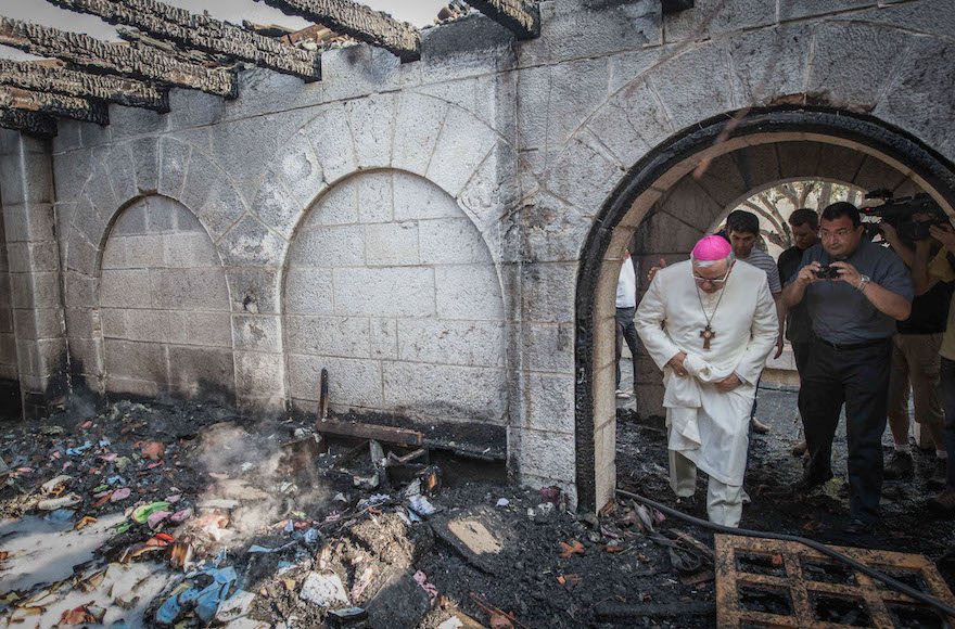 Giacinto-Boulos Marcuzzo, the Roman Catholic Auxiliary Bishop of the Latin Patriarch of Jerusalem, inspecting the torched Church of the Multiplication at Tabgha, June 18, 2015. (Basel Awidat/Flash90)