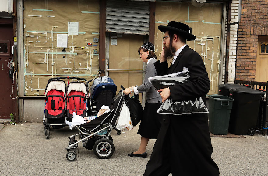 Members of the Jewish Orthodox community walk down a street in a Brooklyn neighborhood on June 14, 2012, in New York City. (Spencer Platt/Getty Images)