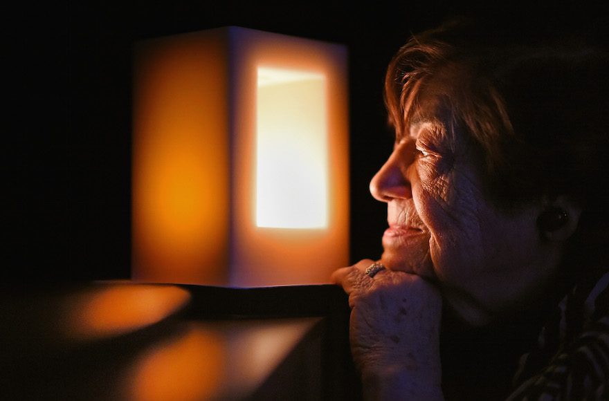 A Holocaust survivor looks at a candle commemorating the liberation of Auschwitz Birkenau, January 27, 2015, in Ayr, Scotland. (Jeff J. Mitchell/Getty Images)
