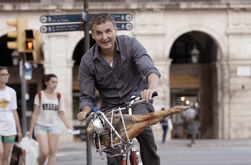 "Rosenthal, biking with a ham in Barcelona, in a scene from ""I'll Have What Phil's Having."" (Courtesy WGBH)"