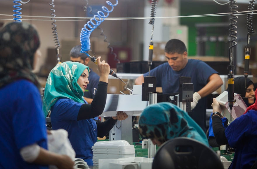 Employees working at the new SodaStream factory built deep in Israel's Negev Desert next to the city of Rahat, Israel, that will replace the West Bank facility when it shuts down in two weeks time, Sept. 2, 2015. (Dan Balilty/AP Images)