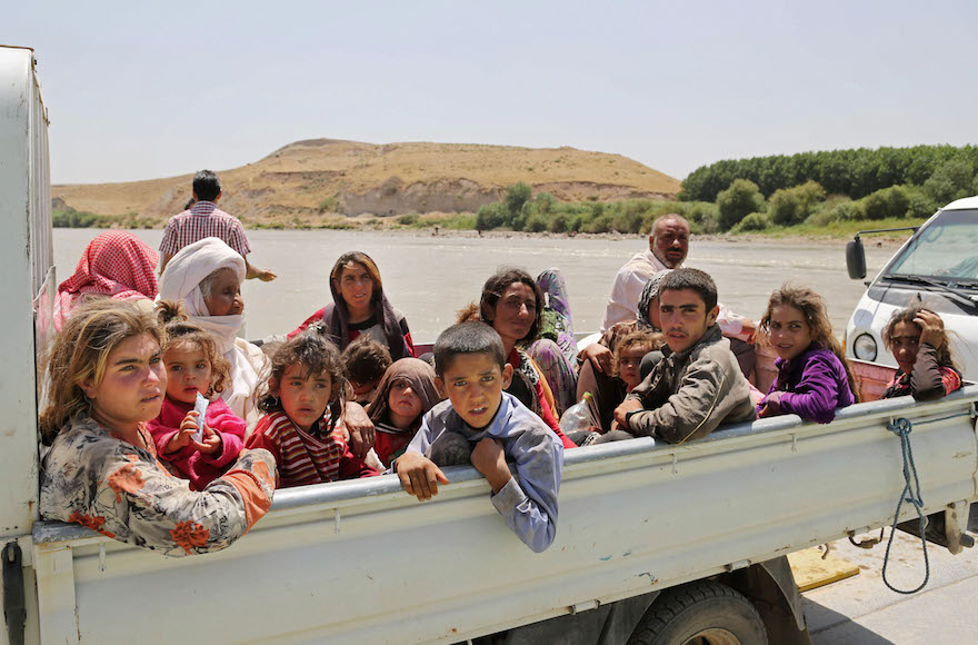 Displaced Iraqis from the Yazidi community cross the Iraq-Syria border, Aug. 10, 2014. (Khalid Mohammed/AP Images)