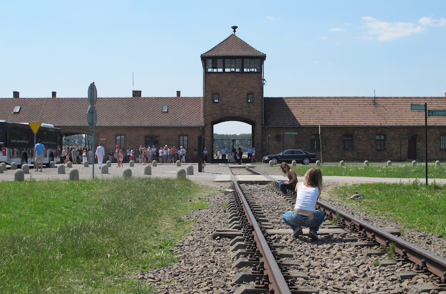 A woman takes a picture of a friend at the looming tower entrance to Birkenau in July 2015. (Ruth Ellen Gruber)