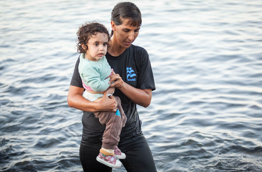 Israel Doctor Tali Shaltiel wades into the water to take a small Syrian child from a dinghy that arrived at a beach in the Greek island of Lesbos. (Boaz Arad/IsraAid)