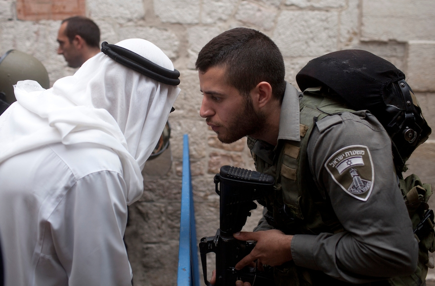 An Israeli border policeman speaking to a Palestinian man next to a stabbing scene in Jerusalem's Old City, October 7, 2015. (Lior Mizrahi/Getty Images)