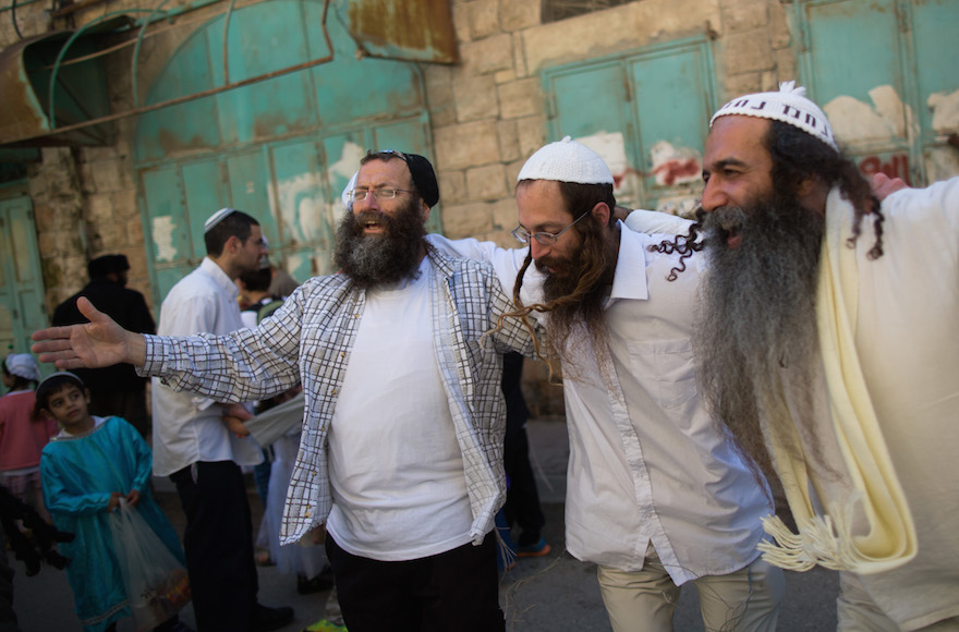 Right-wing activist Baruch Marzel dancing with jewish men during the annual parade marking the Jewish holiday of Purim in the divided West Bank town of Hebron, March 5, 2015. Photo by Yonatan Sindel/Flash90