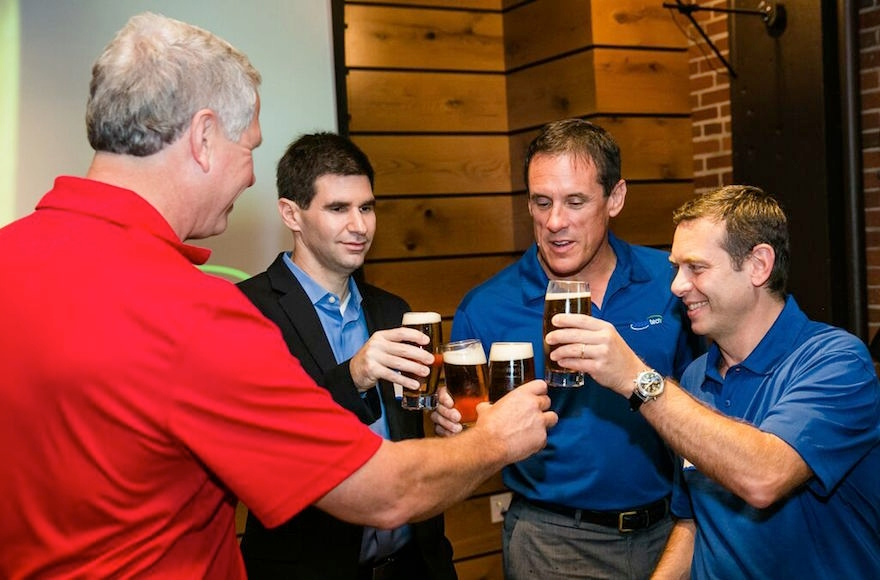 From left, Charlie Storey of Harpoon Brewery and Nadav Efraty, Rick Stover and Francesco Fragasso of Desalitech toasting their production of Charles River Pale Ale. (Nir Landau)