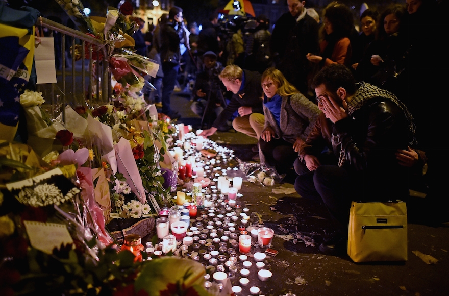 People placing flowers and candles on the pavement near the scene of Friday's Bataclan theater terrorist attack in Paris, Nov. 14, 2015. (Jeff Mitchell/Getty Images)
