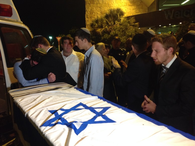 Friends and classmates gather around the coffin of slain yeshiva student Ezra Schwartz at Ben Gurion Airport before it is flown back to Massachusetts. (JTA Photo/Ben Sales)