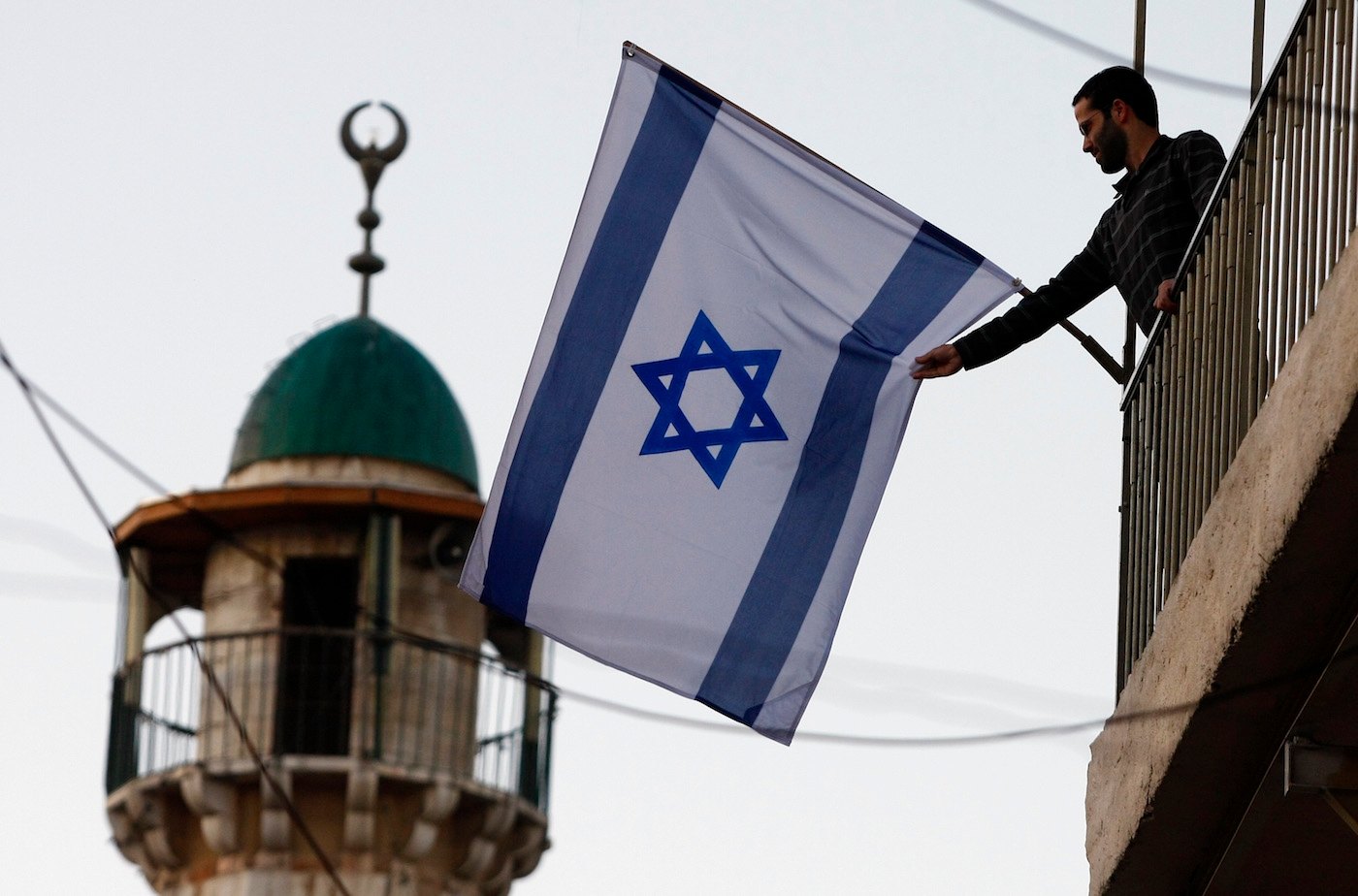 An Israeli Jew raises a flag near the Old City of Jerusalem. Jewish residents in the Old City and predominantly Arab areas nearby have increased 40 percent since 2009. (Abir Sultan/Flash 90)