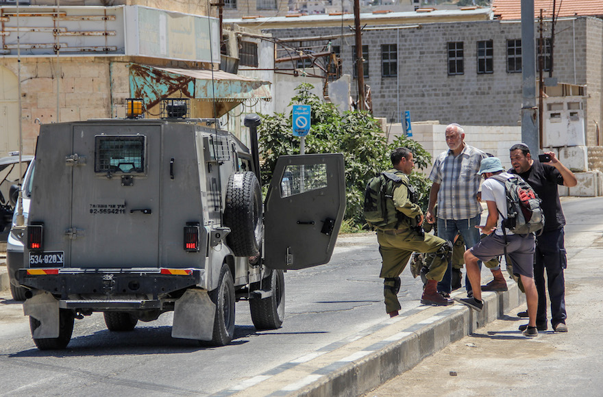 Israeli settlers record a video and argue with a member of Breaking the Silence group on Al-Shuhada Street in the West Bank city of Hebron, July 10, 2015. (Garrett Mills/Flash90)