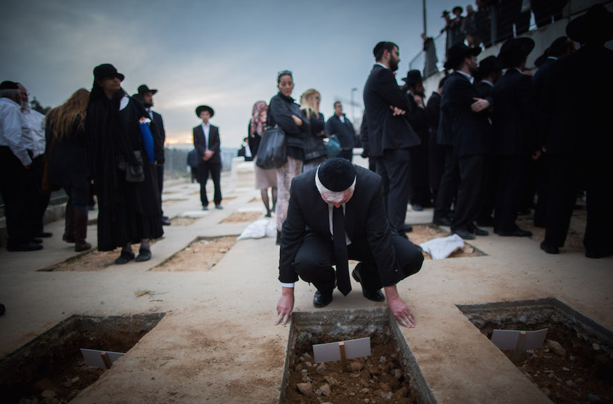 A mourner near the fresh graves of the seven children from the Sassoon family during their funeral in Jerusalem, March 23, 2015. (Yonatan Sindel/Flash90)