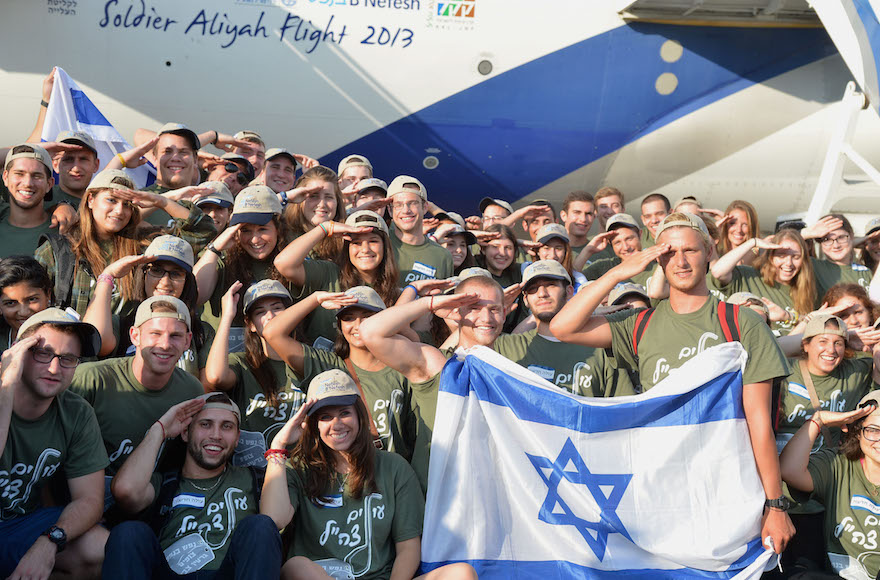 "New immigrants from the U.S. and Canada saluting and holding up Israeli flags as they arrive on a special ""Soldier Aliyah Flight 2013"" on behalf of the Jewish Agency and the Nefesh B'Nefesh organization, at Ben Gurion airport in central Israel, Aug. 13, 2013. (Yossi Zeliger/Flash90)"