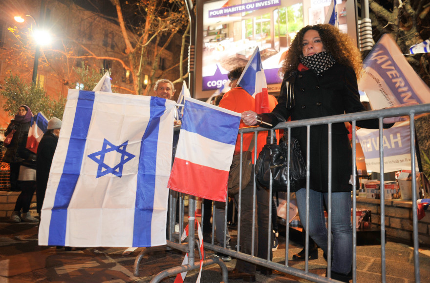 Members of France's Jewish community wave Israeli and French flag, and light memorial candles at a ceremony outside the Hyper Cacher supermarket in Paris, a year after four Jewish shoppers were killed in a terror attack on the store. (Flash90 photo/Serge Attal)