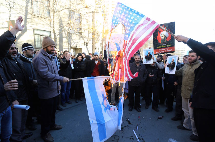 Iranian men burning Israeli and American flags during a demonstration against the execution of prominent Shiite cleric Nimr al-Nimr by Saudi authorities, Jan. 3, 2016. (ATTA KENARE/AFP/Getty Images)