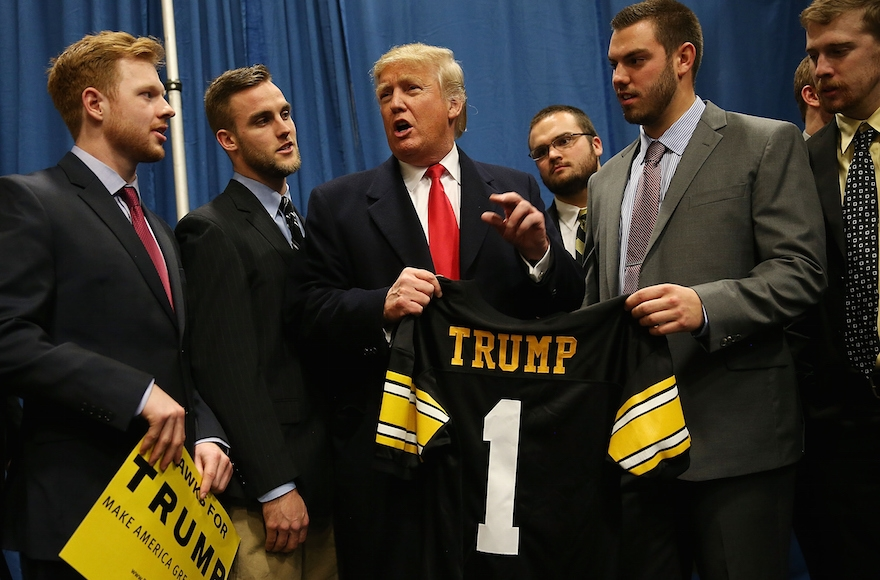 Republican presidential candidate Donald Trump talking with University of Iowa football players during a campaign event in Iowa City, Jan. 26, 2015. (Joe Raedle/Getty Images)