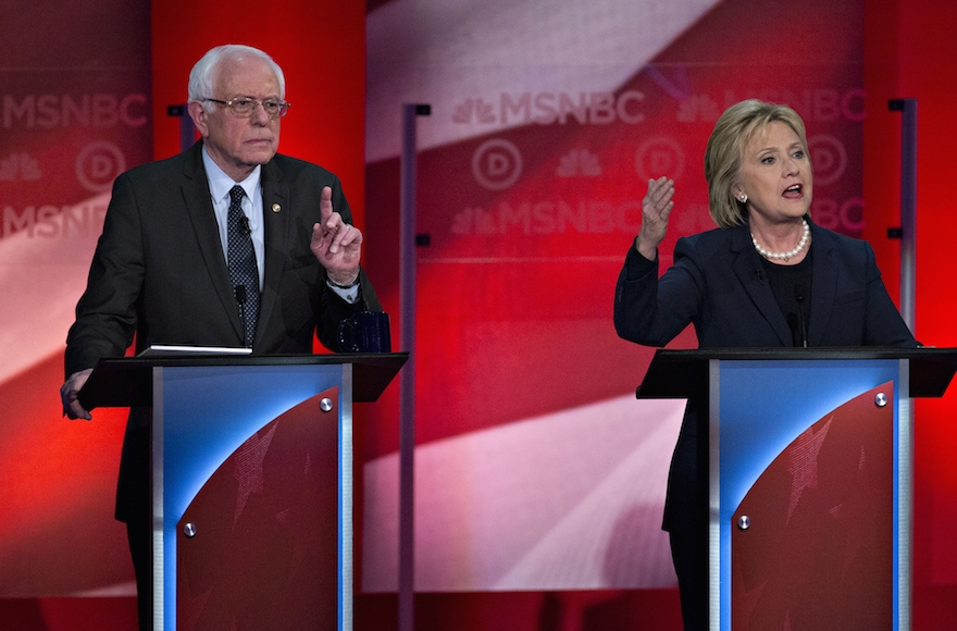 Hillary Clinton speaking as Senator Bernie Sanders listens during the Democratic presidential candidate debate at the University of New Hampshire in Durham, New Hampshire, Feb. 4, 2016. (Andrew Harrer/Bloomberg)