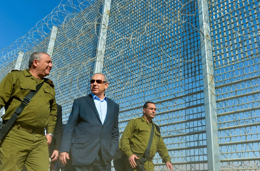 Israeli Prime Minister Benjamin Netanyahu walking with Israel Defense Forces Chief of Staff Gadi Eizenkott, left, as they visit the construction work on the fence between Israel and Jordan, Feb. 9, 2016. (Kobi Gideon/GPO)