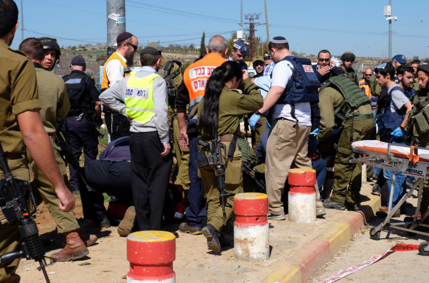 Israeli security forces and rescue personnel at the scene of a terror attack at Gush Etzion Junction, on Feb. 24, 2016. A 23-year-old Israeli man was critically injured by gunfire meant to stop a Palestinian assailant in a stabbing attack; the assailant also was hit. (Gershon Elinson/FLASH90)