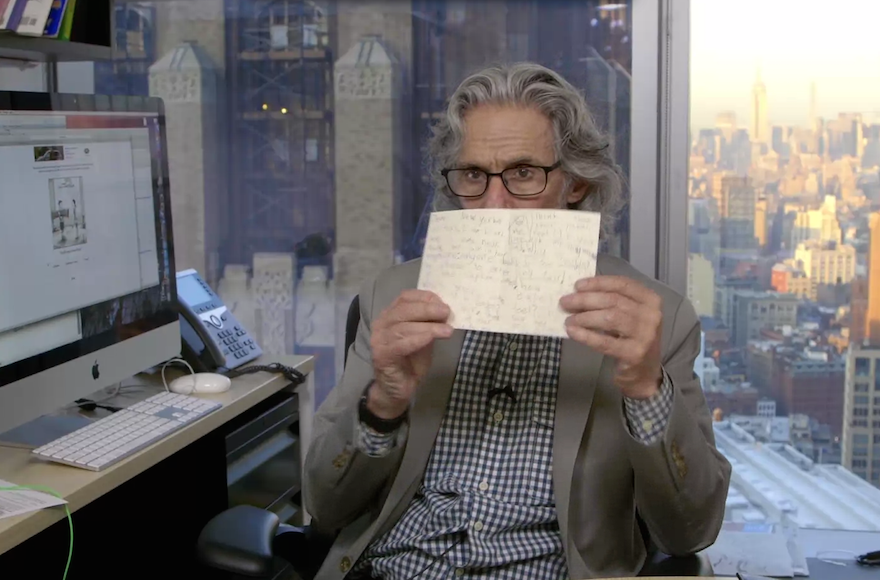 New Yorker cartoon editor Bob Mankoff in his office holding a letter from Jill Jacobs' daughter. (Screenshot from The New Yorker)