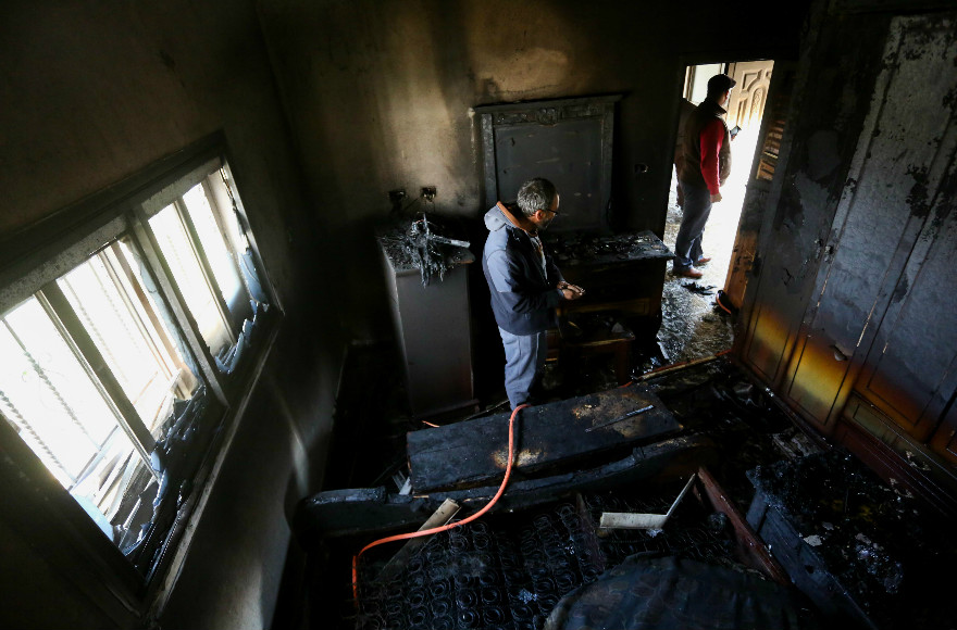 Local residents survey the inside of a burnt out house in the Palestinian village of Duma on March 20, 2016,beloning to the only witness to a July 2015 arson attack allegedly by Jewish extremists that killed three members of one family. (Photo/Flash90)