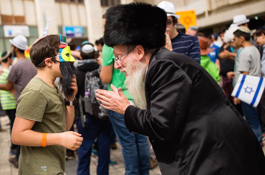 An ultra orthodox jewish man talks to a young Jewish Israeli in central Jerusalem, March 13, 2016. (Corinna Kern/Flash90)