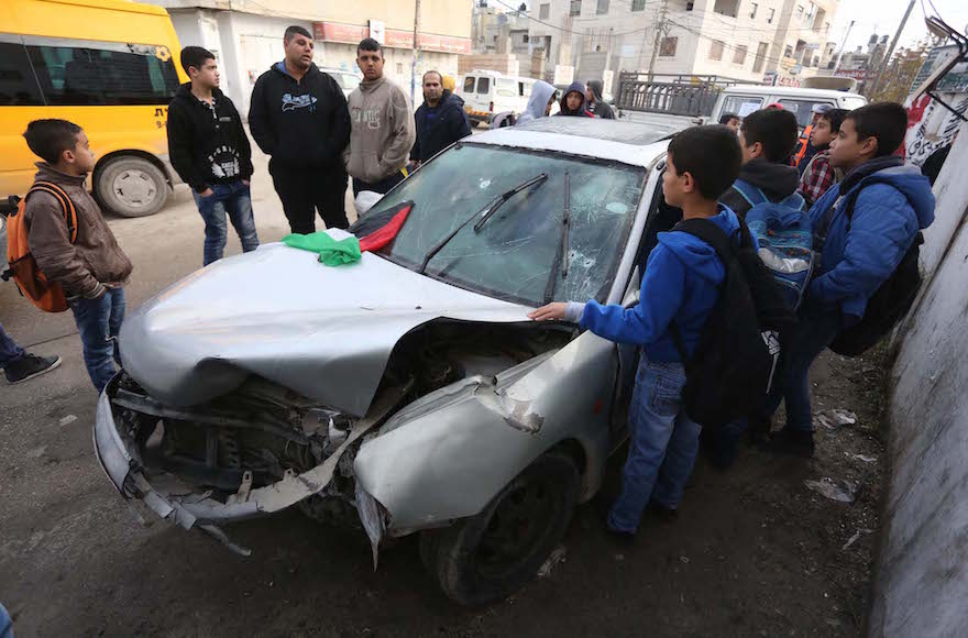 Palestinians looking at a car used in an attempted ramming attack on Israeli soldiers in the Qalandia refugee camp, north of Jerusalem, Israel, Dec. 16, 2015. (Flash90)