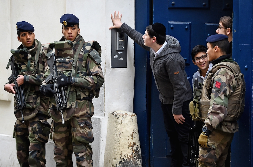 Children looking out from a doorway as armed soldiers patrol outside a school in the Jewish quarter of the Marais district of Paris, Jan. 13, 2015. Jeff J Mitchell/Getty Images)
