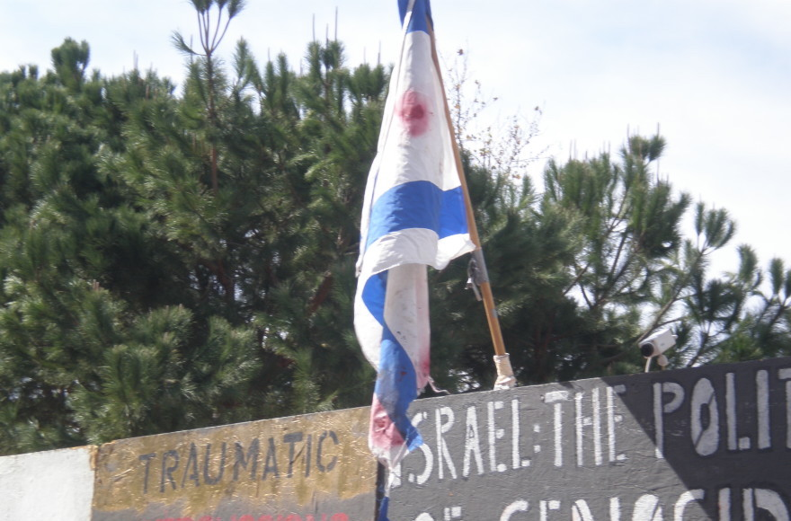 "At UCLA, during the last week of February 2010, a blood-stained Israeli flag was hoisted atop an ""apartheid wall."" (Stand With Us)"