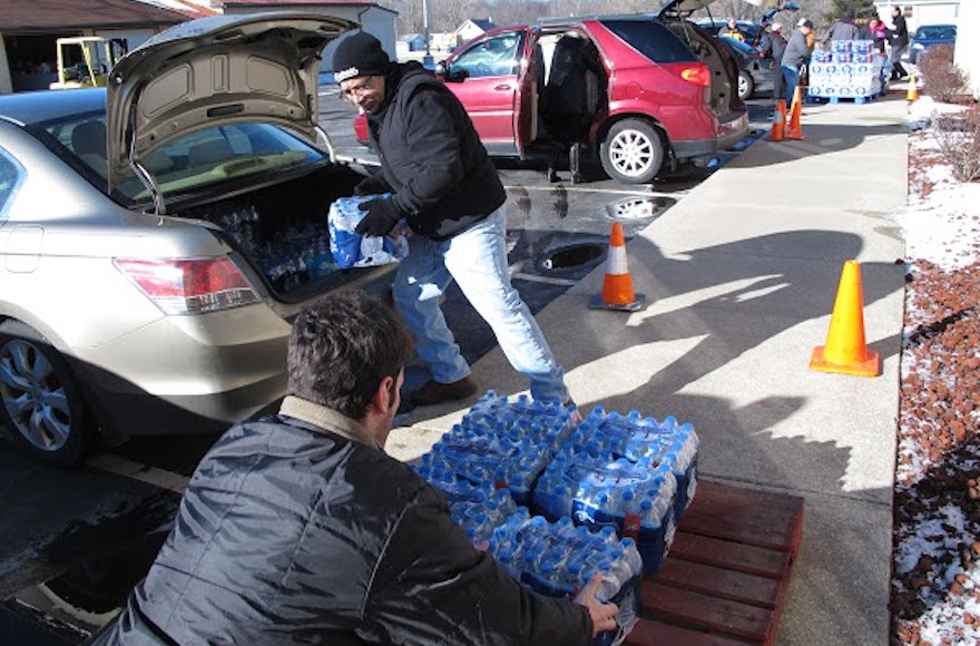 Volunteers offloading water donated by the Flint Jewish community to a local church. (Courtesy of Flint Jewish Federation)