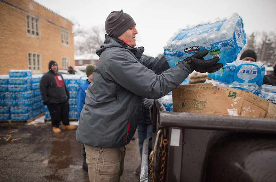 Volunteers loading cases of free water into waiting vehicles at a water distribution center in Flint, Mich., March 5, 2016. (GEOFF ROBINS/AFP/Getty Images)