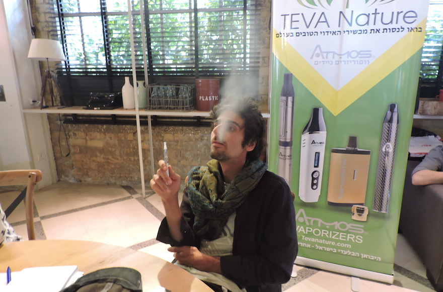 Arnon Tamir, CEO of Teva Nature, smoking a cannabis extract through an electronic cigarette. (Ben Sales)