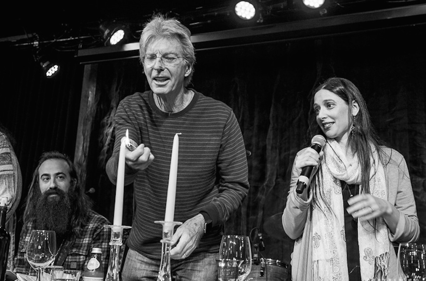 Phil Lesh lights the candles as Jeannette Ferber, a cantorial soloist at Berkeley's Renewal congregation Chochmat HaLev, sings the blessing, and guitarist Ross James looks on. (© Bob Minkin Photography / www.minkinphotography.com)