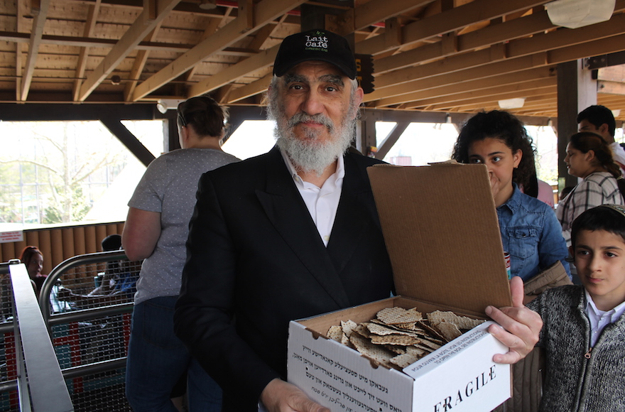 Pinchas Cohen, a restaurateur and father of nine from Brooklyn, brought his own box of handmade shmura matzah to the amusement park for Passover, April 25, 2016. (Uriel Heilman)
