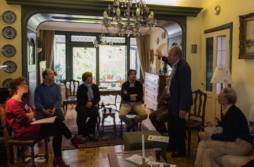 Kees van den Heuvel, standing, talking to guests about the Jewish family that once lived in what is now his home in the town of Vught, the Netherlands, April 30, 2016. (Cnaan Liphshiz)