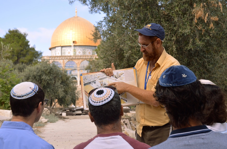 On a tour of the Temple Mount, Yehuda Glick shows religious Jews a diagram of the Jewish temple, which once stood where the golden Dome of the Rock stands today in Jerusalem, Sept. 17, 2013. (Christa Case Bryant/The Christian Science Monitor/Getty Images)